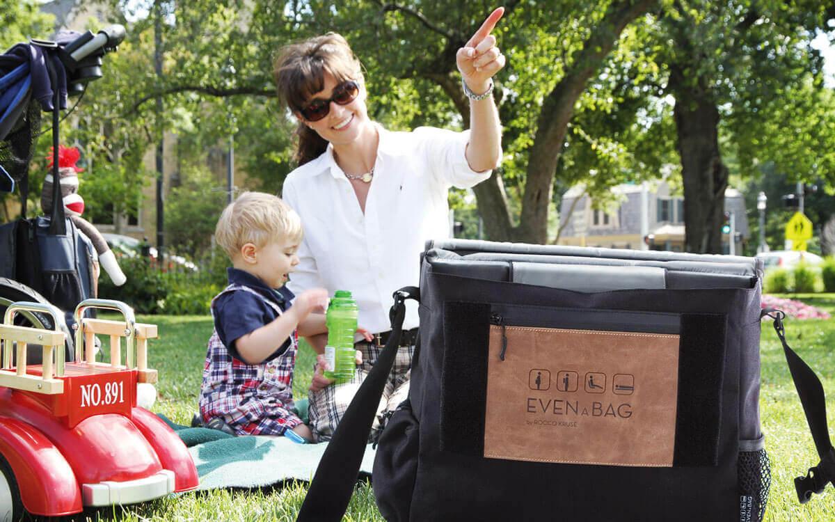 Familie mit Wickeltasche beim Picknick im Park